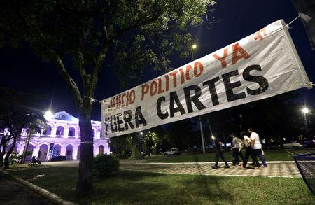 People walk behind a banner that reads outside the Congress in Asuncion