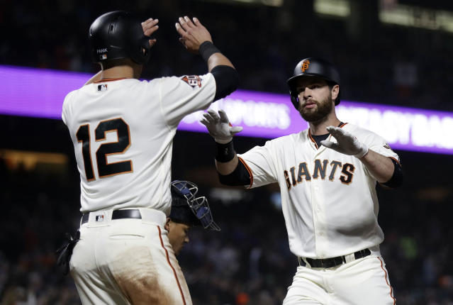San Francisco Giants' Brandon Belt, right, is met at the plate after driving in teammates Joe Panik (12) with a two-run home run during the third inning of a baseball game against the Washington Nationals Tuesday, April 24, 2018, in San Francisco. (AP Photo/Marcio Jose Sanchez)