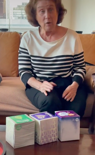 grandma sheila with 3 boxes of tissues on a coffee table in front of her