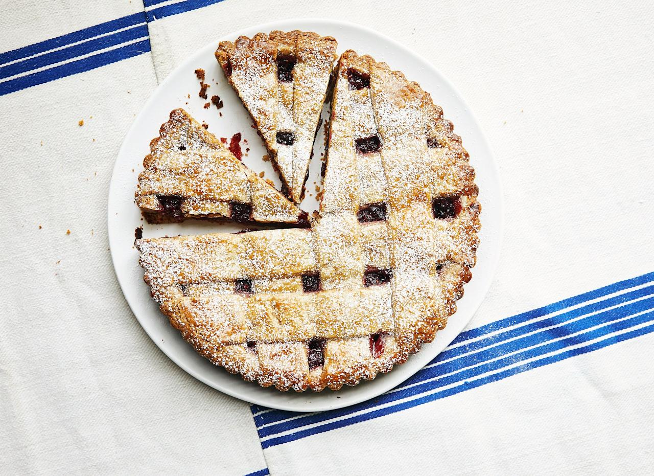 """Inside two layers of buttery, crumbly walnut crust hides a tart cranberry filling. This dough is too delicate to weave into a true lattice without breaking. Instead, arrange the strips in a crosshatch pattern, crossing over in a few places (it will look just as pretty). <a href=""""https://www.bonappetit.com/recipe/cranberry-linzer-tart?mbid=synd_yahoo_rss"""">See recipe.</a>"""