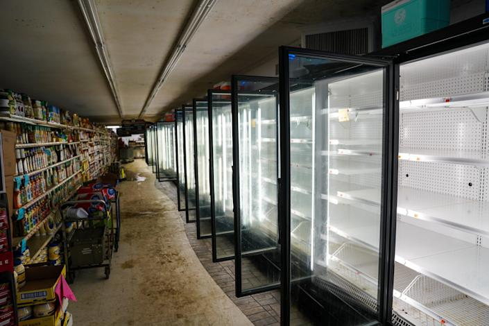 Refrigerator cases sit empty inside the Sureway Supermarket in Grand Isle, Louisiana, after Hurricane Ida knocked out power to the island, spoiling the food.