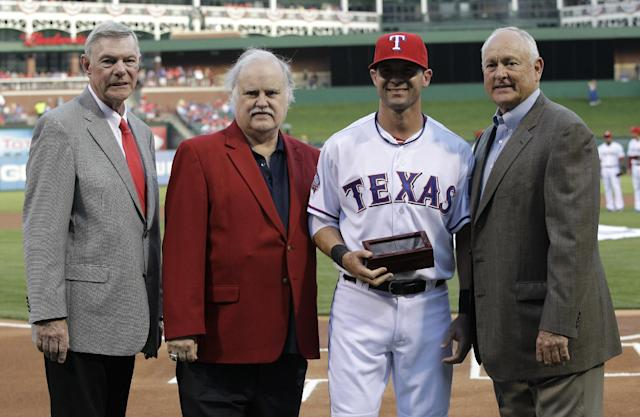 Texas Rangers owners Ray Davis, from left, Bob Simpson, infielder Michael Young, and CEO and President Nolan Ryan, right, during a ceremony where the team received their American League Championship rings before a baseball game against the Chicago White Sox Saturday, April 7, 2012, in Arlington, Texas. (AP Photo/Tony Gutierrez)