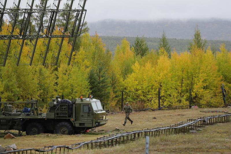 """A Russian soldier runs towards a Nebo-M radar deployed by a forest, during a military exercises on training ground """"Telemba"""", about 80 kilometers (50 miles ) north of the city of Chita during the military exercises Vostok 2018 in Eastern Siberia, Russia, Wednesday, Sept. 12, 2018. Hundreds of thousands Russian troops swept across Siberia on Tuesday in the nation's largest ever war games also joined by China — a powerful show of burgeoning military ties between Moscow and Beijing amid their tensions with the U.S. (AP Photo/Sergei Grits)"""