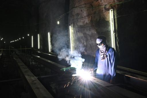 A worker welds a metal pathway at the site