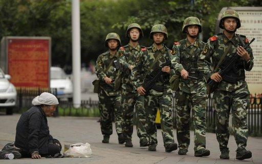 File photo shows a Muslim Uighur woman begging as Chinese paramilitary police march past on a street in Urumqi. Many Uighurs accuse China's rulers of religious and political persecution, while complaining that their homeland is being inundated with the nation's dominant Han ethnic group