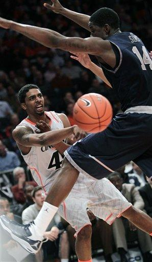 Cincinnati's Jaquon Parker, left, passes around Georgetown's Henry Sims during the quarterfinal round of the Big East NCAA college basketball conference tournament in New York, Thursday, March 8, 2012. (AP Photo/Seth Wenig)