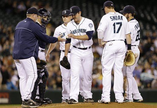 Seattle Mariners starting pitcher Joe Saunders, center, hands the baseball to manager Eric Wedge while being relieved in the second inning of a baseball game against the Pittsburgh Pirates on Tuesday, June 25, 2013, in Seattle. (AP Photo/Elaine Thompson)