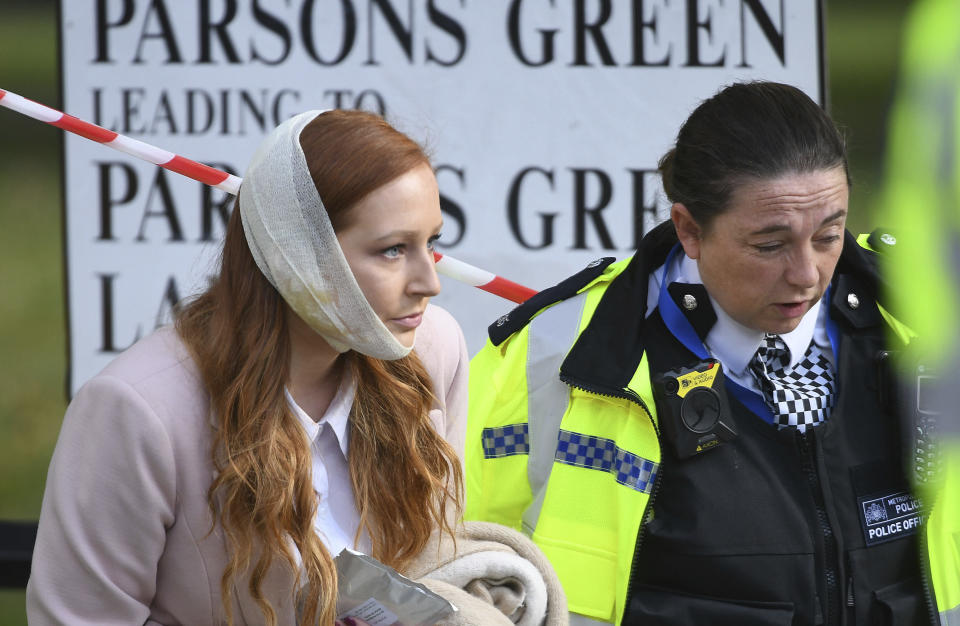 An injured woman being assisted by a police officer close to Parsons Green station after this morning's blast (Stefan Rousseau/PA via AP)