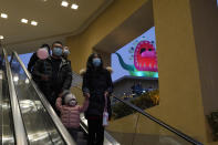 Visitors to a mall with a monster themed festival wears masks to protect from the coronavirus in Beijing Saturday, Dec. 26, 2020. Beijing has urged residents not to leave the city during the Lunar New Year holiday in February, implementing new restrictions after several coronavirus infections last week. (AP Photo/Ng Han Guan)
