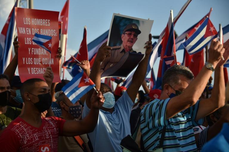 A supporter of the Cuban government holds a portrait of Cuban former President Raul Castro during a demonstration in Havana on July 17, 2021