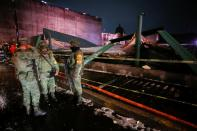 """Soldiers chat at a scene where the roof protecting the """"Casa de las Aguilas"""", part of the ruins of the Templo Mayor archaeological site, collapsed after heavy rain and hail, in Mexico City"""