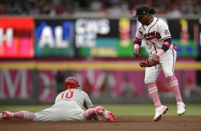Philadelphia Phillies' J.T. Realmuto, left, steals second base as Atlanta Braves' Ozzie Albies watches during the first inning of a baseball game Sunday, May 9, 2021, in Atlanta. (AP Photo/Ben Margot)