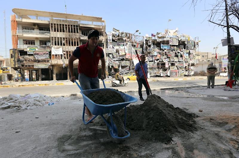 Iraqi workers rebuild on July 31, 2016 a shop that was damaged in a bombing in Baghdad's Karrada Dakhil street in the capital's commercial Karrada district (AFP Photo/SABAH ARAR)