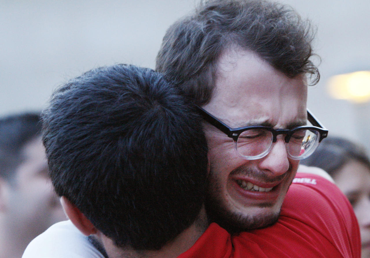 Boston University student Blake Wrobbel, of Los Angeles, right, gets emotional during a candlelight vigil on Marsh Plaza at Boston University, Saturday, May 12, 2012, for three students studying in New Zealand who were killed when their minivan crashed during a weekend trip. Daniela Lekhno, 20, of Manalapan, N.J.; Austin Brashears, 21, of Huntington Beach, Calif.; and Roch Jauberty, 21, whose parents live in Paris, were killed as they travel in a minivan at about 7:30 a.m. Saturday near the North Island vacation town of Taupo when the vehicle drifted to the side of the road and then rolled when the driver tried to correct course. (AP Photo/Bizuayehu Tesfaye)