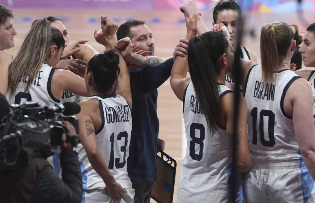 ADDS REASON WHY ARGENTINA IS OUT OF THE MEDAL ROUND - Argentina's coach Leonardo Costa, center, comforts his players during the women's basketball match against the Virgin Islands at the Pan American Games in Lima, Peru, Thursday, Aug. 8, 2019. Argentina's women's basketball team had to forfeit its match against Colombia at the Pan American Games on Wednesday for wearing the wrong uniform color. Argentina won todays match against the Virgin Islands but is out of the medal rounds because of the uniform blunder. (AP Photo/Martin Mejia)