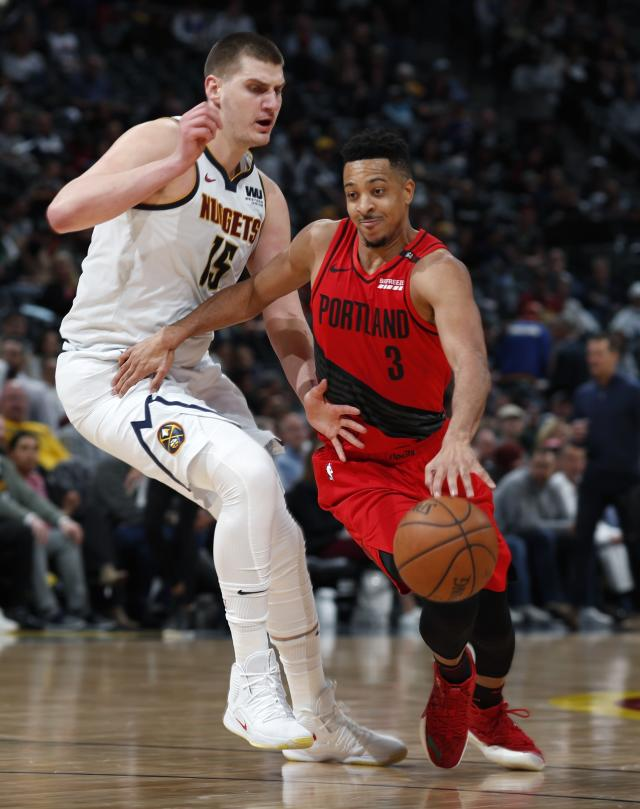 Portland Trail Blazers guard CJ McCollum, right, drives by Denver Nuggets center Nikola Jokic during the second half of Game 2 of an NBA basketball second-round playoff series Wednesday, May 1, 2019, in Denver. Portland won 97-90. (AP Photo/David Zalubowski)