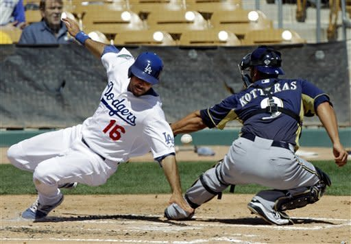Los Angeles Dodgers' Andre Ethier (16) avoids Milwaukee Brewers catcher George Kottaras to score on a double by James Loney in the first inning of a spring training baseball game Tuesday, March 20, 2012, in Glendale, Ariz. (AP Photo/Mark Duncan)