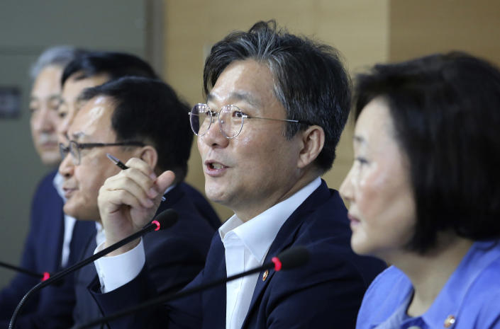 Sung Yun-mo, second from right, South Korea's minister of Trade, Industry and Energy, speaks during a press conference at the government complex in Seoul, South Korea, Monday, Aug. 5, 2019. Sung said South Korea will spend 7.8 trillion won ($6.5 billion) over the next seven years to develop technologies for industrial materials and parts as it moves to reduce its dependence on Japan during an escalating trade row. The announcement came days after Japan's Cabinet approved the removal of South Korea from a list of countries with preferential trade status. (AP Photo/Ahn Young-joon)