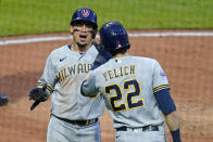 Milwaukee Brewers' Willy Adames, left, and Christian Yelich (22) celebrate after scoring on a triple by Tyrone Taylor off Pittsburgh Pirates starting pitcher JT Brubaker during the sixth inning of a baseball game in Pittsburgh, Friday, July 2, 2021. (AP Photo/Gene J. Puskar)