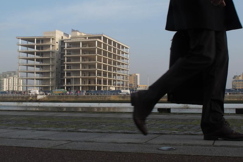 FILE - In this Thursday, March 22, 2012 file photo, a commuter walks past the abandoned, unfinished headquarters of Anglo Irish Bank in Dublin. The Irish government is ending its guarantee to insure bank bondholders against losses, a move that reflects growing confidence that the country's three main banks can survive on their own. Ireland's emergency 2008 decision to insure bank bondholders against potential losses failed to shore up confidence in its banks — and ended up bankrupting the nation. But Ireland this year is taking steps to repair its credit rating and exit its own 2010 international bailout.  The decision made Tuesday, Feb. 26, 2013 by the government,  to end the insurance scheme for foreign investors in Ireland's banks on March 28 offers more evidence that the country is getting ready to resume normal debt financing. (AP Photo/Shawn Pogatchnik, File)