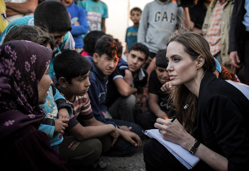 A handout picture made available by the United Nations High Commission for Refugees (UNHCR) shows US actress Angelina Jolie (R) listening to Syrian refugees in a camp on the Jordan-Syria border on June 18, 2013 (AFP Photo/O. Laban-Mattei)