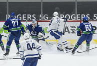 Toronto Maple Leafs' Auston Matthews (34) scores against Vancouver Canucks goalie Braden Holtby (49) as Travis Hamonic (27) and Jalen Chatfield (63) watch during the second period of an NHL hockey game in Vancouver, British Columbia, Sunday, April 18, 2021. (Darryl Dyck/The Canadian Press via AP)