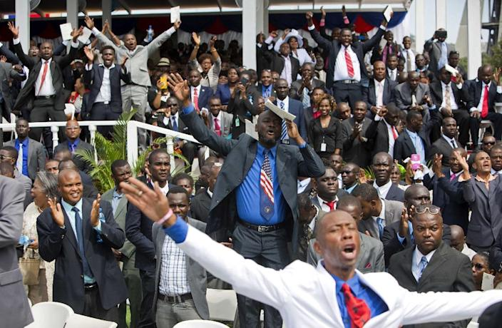 Supporters of Haiti's new President Jovenel Moise cheer as he speaks at the National Palace during his inauguration ceremony in Port-au-Prince, Haiti, Tuesday Feb. 7, 2017. Moise was sworn as president for the next five years after a bruising two-year election cycle, inheriting a struggling economy and a deeply divided society. (AP Photo/Dieu Nalio Chery)