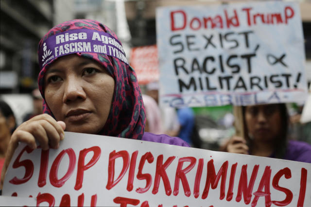 <p>Nur, a protester from Indonesia, holds a sign during a rally as they tried to march near the U.S. Embassy in Manila, Philippines to protest the upcoming visit of President Donald Trump on Thursday, Nov. 9, 2017. (Photo: Aaron Favila/AP) </p>