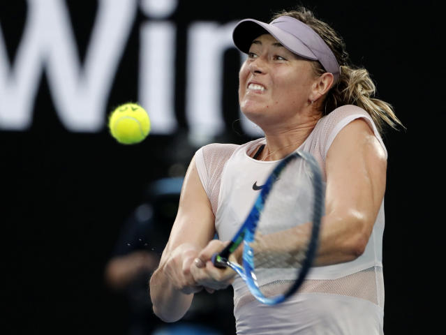 Russia's Maria Sharapova makes a backhand return to Germany's Angelique Kerber during their third round match at the Australian Open tennis championships in Melbourne, Australia, Saturday, Jan. 20, 2018. (AP Photo/Vincent Thian)