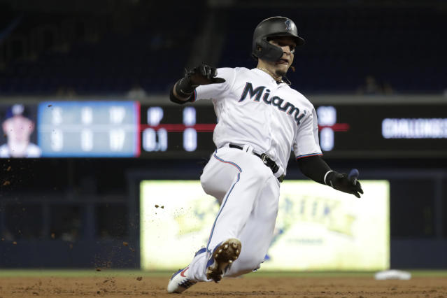 Miami Marlins' Isan Diaz slides safely into third, advancing on a single by Garrett Cooper during the first inning of the team's baseball game against the Milwaukee Brewers, Wednesday, Sept. 11, 2019, in Miami. (AP Photo/Lynne Sladky)