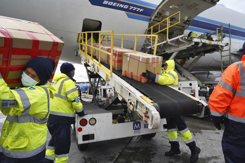 Wearing protective masks, ground crew at the Los Angeles International airport unload supplies of medical personal protective equipment from a China Southern cargo plane upon it's arrival on Friday, April 10, 2020. An Associated Press analysis shows states spent more than $7 billion this spring buying personal protective equipment like masks, gloves and gowns as well as vital medical devices like ventilators. (AP Photo/Richard Vogel)