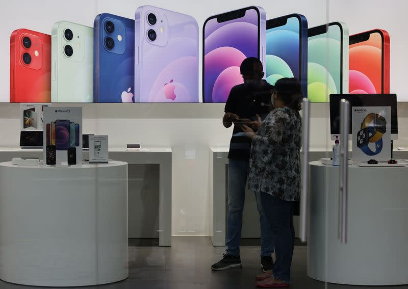 A salesperson speaks to a customer at an Apple reseller store in Mumbai