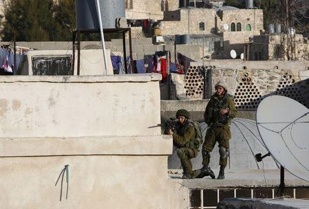 An Israeli soldier aims his weapon at Palestinians as Israeli settlers take over several houses, which are disputed between Palestinians and Israelis, in the West Bank old city of Hebron January 21, 2016.  REUTERS/Mussa Qawasma