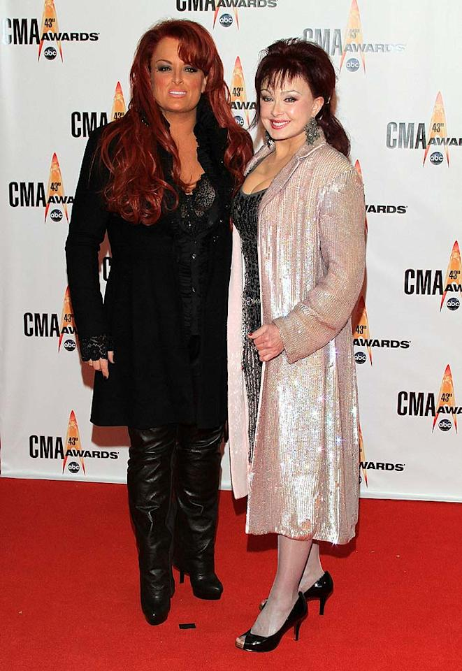 """At this year's CMAs, the Judds donned gaudy gear yet again. Between Wynonna's garish locks and terrible tan and Naomi's sequined eye-sore and horrendous pantyhose, the dubious mother-daughter duo was easily the tackiest twosome of the night. Taylor Hill/<a href=""""http://www.wireimage.com"""" target=""""new"""">WireImage.com</a> - November 11, 2009"""