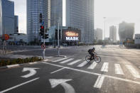 A man rides a bicycle next to a billboard calling people to wear masks, on empty road following new restrictions in the three-week nationwide lockdown, in Tel Aviv, Israel, Saturday, Sept. 26, 2020. (AP Photo/Oded Balilty)