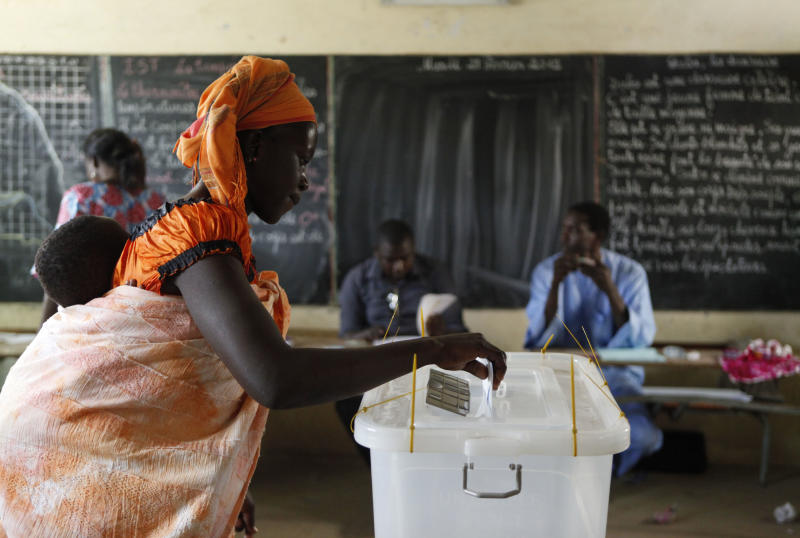 Ramatoulaye Teme carries her son on her back as she casts her vote for president at a polling station in the Pikine suburb of Dakar, Senegal Sunday, Feb. 26, 2012. Polling stations have closed and election monitors in Senegal are now counting ballots from a vote that has tested the nation's image as one of the continent's oldest and most robust democracies. Sunday's election follows weeks of protests after the country's highest court ruled 85-year-old President Abdoulaye Wade could run for a third term. (AP Photo/Rebecca Blackwell)