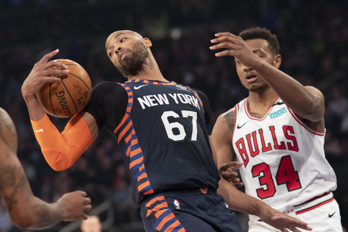 New York Knicks center Taj Gibson (67) pulls down a rebound in front of Chicago Bulls center Wendell Carter Jr. (34) during the first half of an NBA basketball game, Saturday, Feb. 29, 2020 in New York. (AP Photo/Mark Lennihan)
