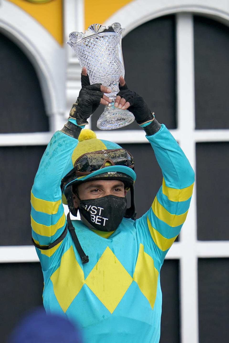 Joel Rosario holds a trophy after he rode Army Wife to win the Black-Eyed Susan Stakes horse race at Pimlico Race Course, Friday, May 14, 2021, in Baltimore. (AP Photo/Julio Cortez)
