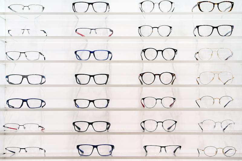 Stand with glasses in the store of optics, eye concept. Close-up many glasses on a stand.