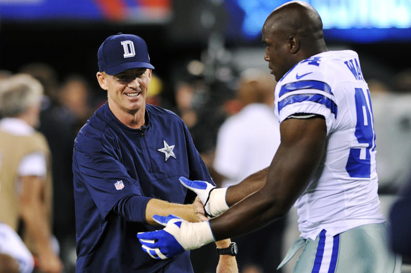 Dallas Cowboys head coach Jason Garrett, left, talks to linebacker DeMarcus Ware before an NFL football game against the New York Giants, Wednesday, Sept. 5, 2012, in East Rutherford, N.J. (AP Photo/Bill Kostroun)