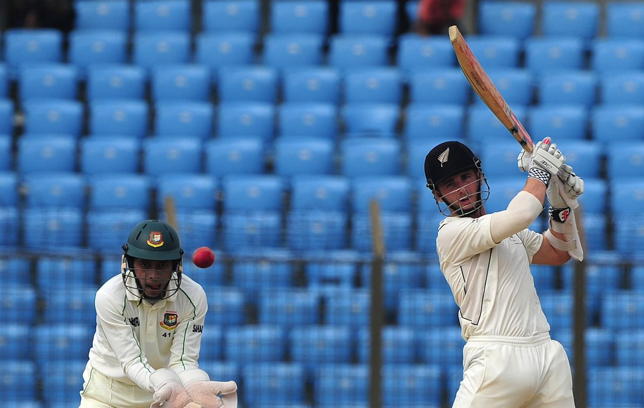 New Zealand batsman Kane Williamson (R) plays a shot as Bangladesh captain Mushfiqur Rahim looks on during the fourth day of the first Test match between Bangladesh and New Zealand at The Zahur Ahmed Chowdhury Stadium in Chittagong on October 12, 2013.  AFP PHOTO/Munir uz ZAMANh        (Photo credit should read MUNIR UZ ZAMAN/AFP/Getty Images)