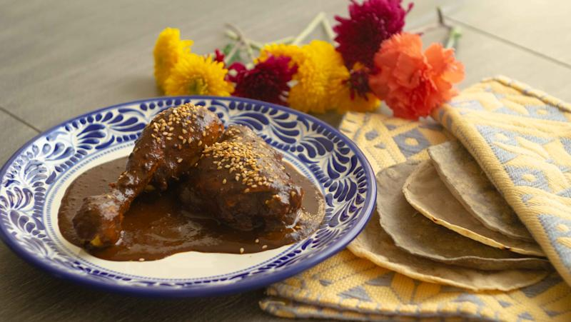 A wooden blue table with multi-colored flowers, corn tortillas inside a yellow cloth, and a blue and white Mexican plate with two pieces of chicken covered with Mexican mole sauce and sesame on top.