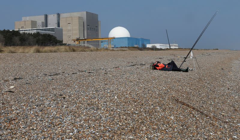 FILE PHOTO: A fisherman takes a nap on Sizewell beach outside Sizewell nuclear power station in Suffolk, eastern England