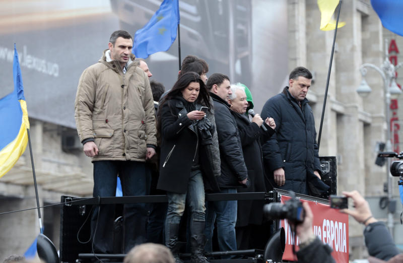 Polish politician Jaroslaw Kaczynski, second right, speaks as lawmaker and chairman of the Ukrainian opposition party Udar (Punch), WBC heavyweight boxing champion Vitali Klitschko, left, watches during a rally in downtown Kiev, Ukraine, on Sunday, Dec. 1, 2013. As many as 100,000 demonstrators chased away police to rally in the center of Ukraine's capital on Sunday, defying a government ban on protests on Independence Square, in the biggest show of anger over the president's refusal to sign an agreement with the European Union. (AP Photo/Ivan Sekretarev)