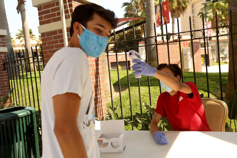 LOS ANGELES, CA - AUGUST 17, 2020 - - Anthony Steimle, 21, left, has his temperature checked by Campus Health and Screening Ambassador Avery Theus, 23, on the first day of academic instruction at USC for the Fall 2020 semester in Los Angeles on August 17, 2020. Steimle, not a student at USC, was visiting the campus with his brother. All students and visitors to the campus have to go through a wellness check, answer questions regarding COVID-19 symptoms and have their temperature checked before they are allowed to enter campus. (Genaro Molina / Los Angeles Times via Getty Images)