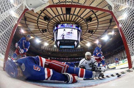 Jun 9, 2014; New York, NY, USA; New York Rangers defenseman Dan Girardi (5) falls over the back of goalie Henrik Lundqvist (rear) and sweeps the puck off the goal line and away from Los Angeles Kings right wing Marian Gaborik (12) during the third period in game three of the 2014 Stanley Cup Final at Madison Square Garden. Mandatory Credit: Bruce Bennett/Pool Photo via USA TODAY Sports