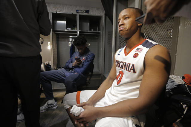 Virginia's Devon Hall (0) takes questions from the media in the locker room after losing to UMBC in a first-round game in the NCAA men's college basketball tournament in Charlotte, N.C., Friday, March 16, 2018. (AP Photo/Bob Leverone)