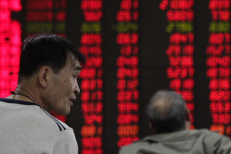 Investors monitor stock prices at a brokerage house in Beijing, Monday, April 8, 2019. Shares are mixed in Asia, after trade talks between China and the U.S. wrapped up with officials on both sides claiming progress. (AP Photo/Andy Wong)