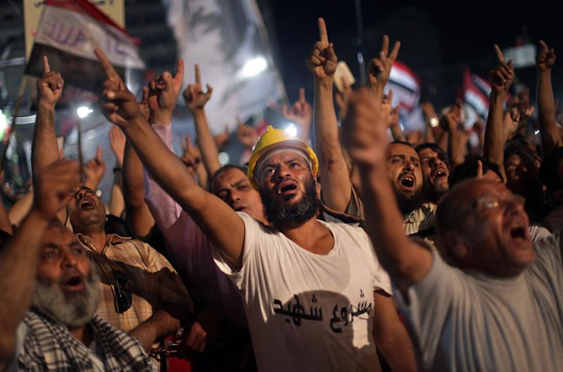 """Supporters of Egypt's ousted President Mohammed Morsi chant slogans during a protest outside Rabaah al-Adawiya mosque, where they have installed a camp and hold daily rallies at Nasr City, in Cairo, Egypt, Wednesday, July 31, 2013. Egypt's military-backed government has ordered the police to break up the sit-in protests by supporters of ousted President Mohammed Morsi, saying they pose an """"unacceptable threat"""" to national security. Information Minister Dorreya Sharaf el-Din said in a televised statement Wednesday that the police are to end the demonstrations """"within the law and the constitution."""" The Arabic writing on the white shirt reads """"A martyr project"""". (AP Photo/Khalil Hamra)"""