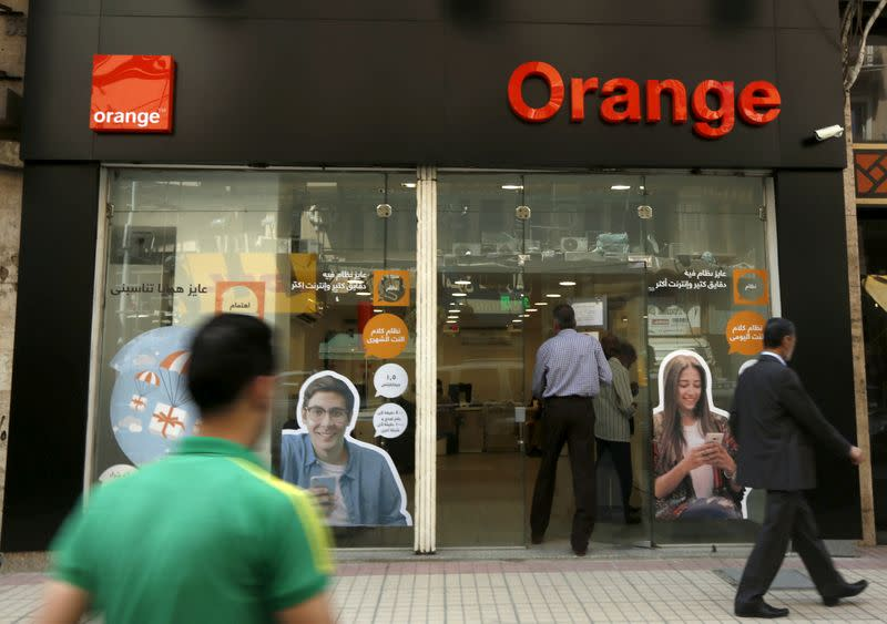 FILE PHOTO: People walk past a shop of French telecom operator Orange in Cairo